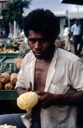Man peeling a pineapple at a fruit stand
