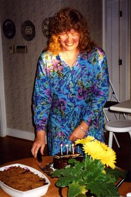 [Unidentified woman in a blue dress smiling behind a cake with three candles]