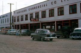 Street with parked cars and the building of Northern Commercial Company, a retail store chain, in...