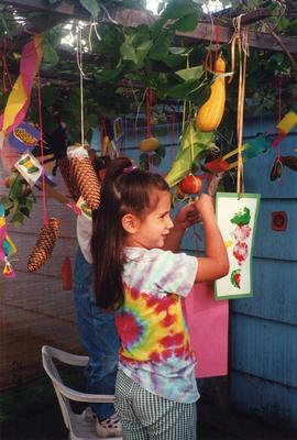 Unidentified girl decorating sukkah