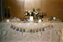 [Table set up with plates, cutlery, flowers and a menorah]