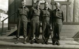 [Three unknown men and Dr. Irving Snider posing for the camera in their army uniform]