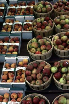 Apples in wooden crates and peaches in cardboard boxes