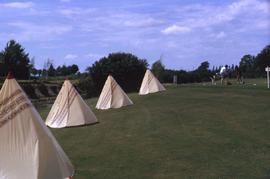 Four teepees on a golf course with two golfers in the background