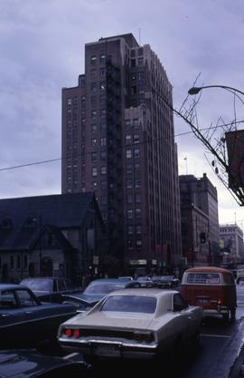 Cars waiting at a light next to buildings and a church in downtown Vancouver