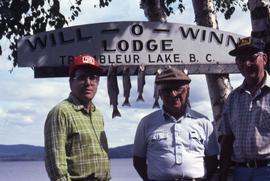 Two unknown men and Dr. Irving Snider posing in front of  a sign with fish hanging
