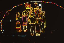 Light display of a group of people holding candles under a piñata against a black sky