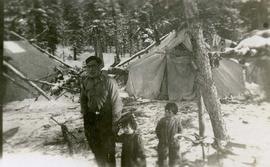[Unknown man and two children standing in front of tents in the snow]