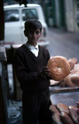 Unidentified boy holding a type of round bread