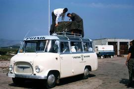 "Two people loading luggage on the roof of a ""PUTNIK BEOGRAD - YUGOSLAVIA"" van"