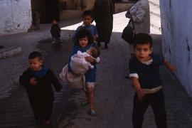 Children running with a girl running in the centre of the group holding a baby