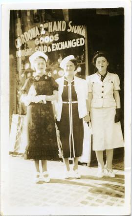 Photograph of [Mary, Bella + Ann Mann] in front of [Cordova 2nd Hand Store Goods]